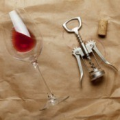 Image of wine glass on it's side with a small amount of wine, cork screw, and cork on a brown paper background with wine stains.