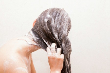 Back view of a woman's sudsy hair as she washes it.