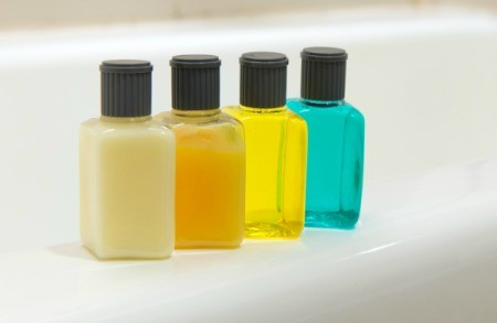 Four small bottles like those you would get of shampoo, conditioner, and lotion at a hotel, lined up on the edge of a tub.