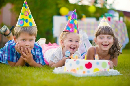 A little boy and two little girls wearing party hats laying their stomaches in the grass in front of a cake