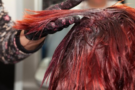 Hair being dyed red at the roots.