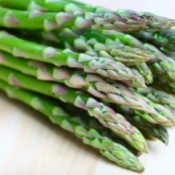 Pile of asparagus spears against a white background