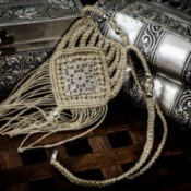 Intricate macrame (finger weaving) necklace resting against silver or pewter boxes on a dark wood surface.
