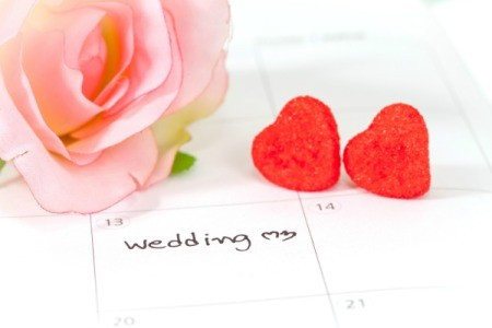 Close-up of large desk calendar with March 13th marked as Wedding with two red hearts and a large pink roses laying on the calendar.