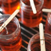 Several jars filled with hot red wax.  Sticks with wicks attached lay across the top of each jar with one end of the wick in the wax