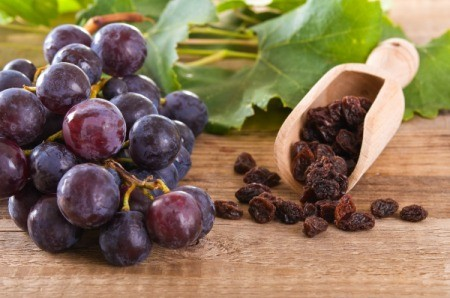 Close up of a bunch of red grapes next to a wooden scoop of raisins on a butcher block surface
