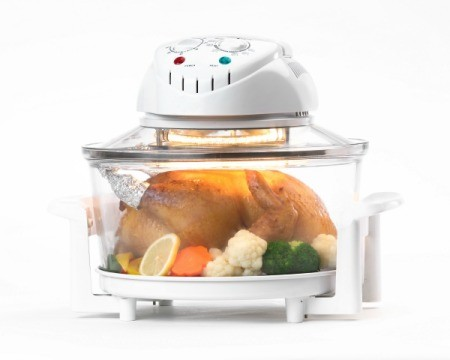 Close up image of an electronic countertop convection oven containing a baked chicken and vegetables against a white background