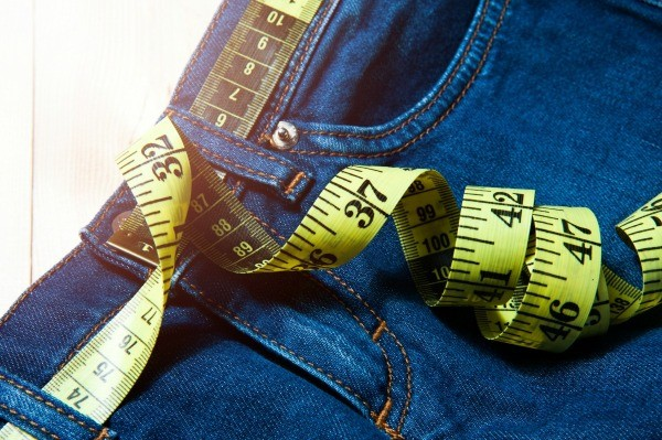 Close-up of a pair of jeans with a measuring tape curled on top and through the belt loop against a wooden background