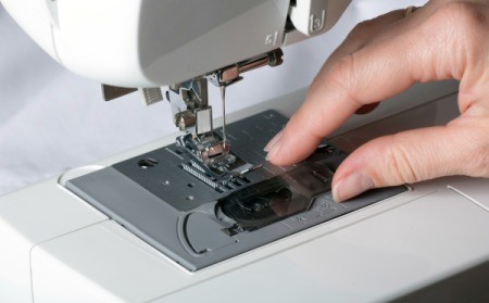 Close-up of a sewing machine with female had touching the standard sewing plate