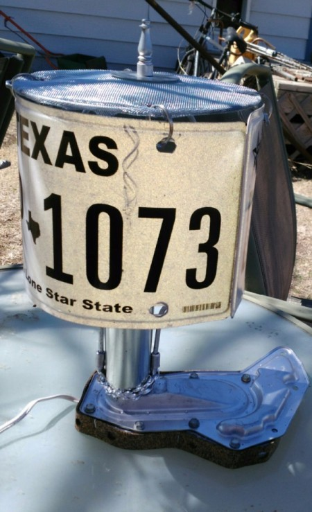 A lamp made with a license plate and other auto parts.
