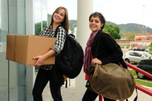 Two college students moving into their dorm.