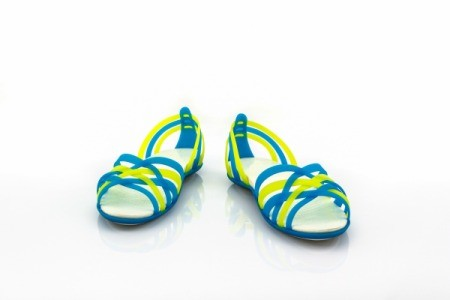 Yellow and blue strappy sandals against a white background