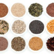 Twelve different types of seeds in white bowls against white background