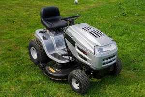 Silver and black riding lawn mower against mown grass background