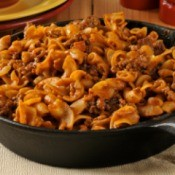 Hamburger, noodle and red sauce casserole in a cast iron skillet