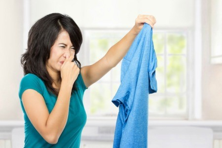 Woman holding blue shirt in hand with a look of obvious disgust and her other hand plugging her nose.
