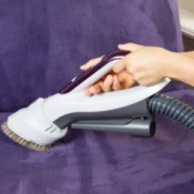 Woman hands using a upholstery attachment to wash a purple suede couch