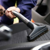 Close up of a vacuum wand with upholstery attachment vacuuming a car seat.