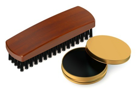 Opened tin of black shoe polish and a brush against a white background