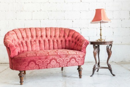 Rose pink vintage couch with wooden side table and table lamp with rose pink shade against white brick background