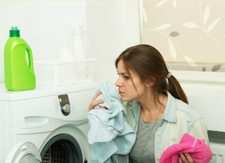 Woman crouched in front of a front loading dryer smelling a shirt