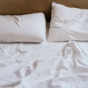Unmade bed with rumpled white sheets
