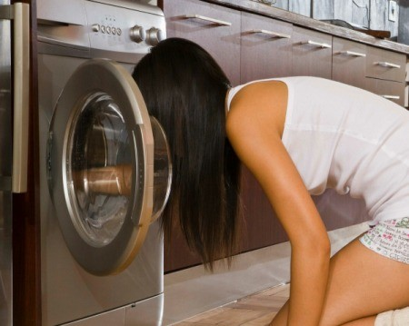 Woman kneeling on floor looking inside dryer