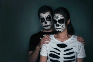 Couple in t-shirts ripped to look like a skeleton and sugar skull facepaint