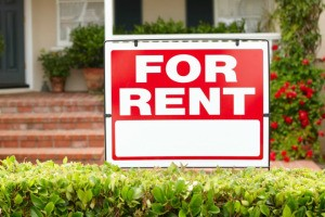 For Rent Sign hanging over a hedge with a home in the background