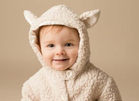 Smiling baby in a Lamb Costume against a beige background