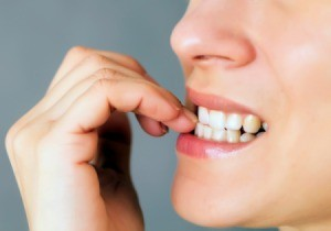 Close up of woman's teeth biting her finger nails