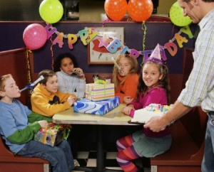 Father bringing birthday cake to birthday girl at a table of tweens (10-12 year-olds) wearing party hats