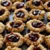 Thumbprint cookies with jam filling on a cookie sheet