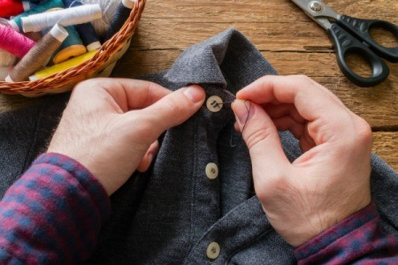 Man's hands sewing button on shirt