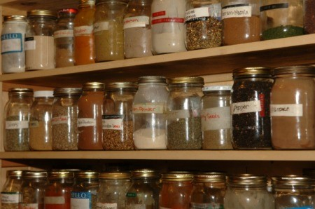 Wide variety of different types and sized of jars filled with spices on three shelves all with different types of labels