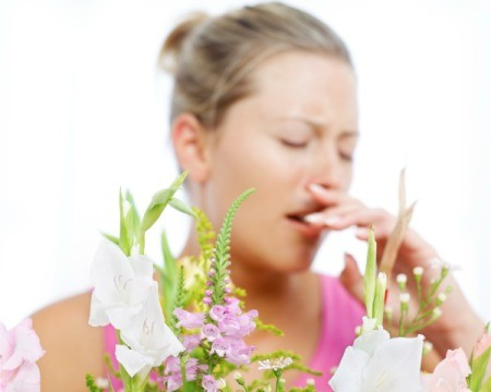 Woman sneezing with flowers in the foreground.
