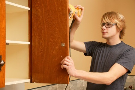 Man sanding kitchen cabinet door