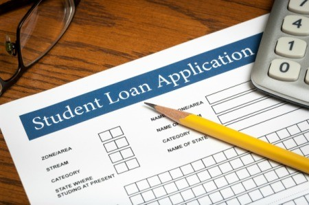 Close up image of student loan application with pencil and calculator