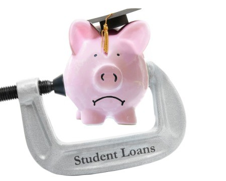 "Frowning piggy bank wearing graduation cap being pressed by a metal clamp labelled ""Student Loans"""