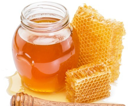 Jar of honey, two honeycomb, and spilled honey against a white background