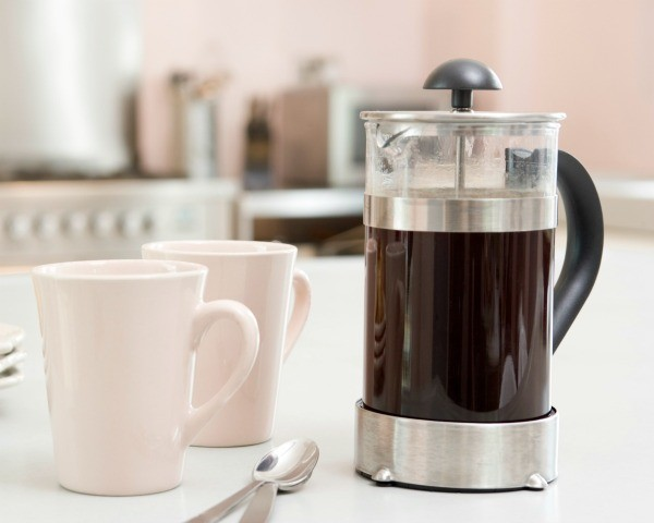 French press containing coffee, two white coffee cups, and two spoons on a white counter top
