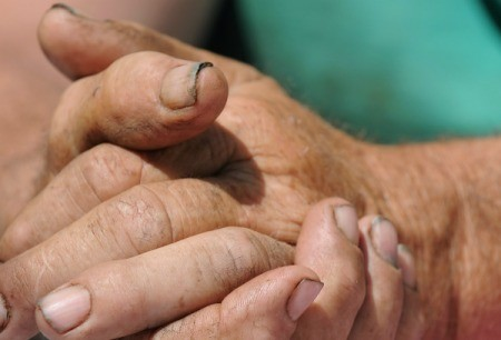 Close up of clasped hands with dirt imbedded under the fingernails