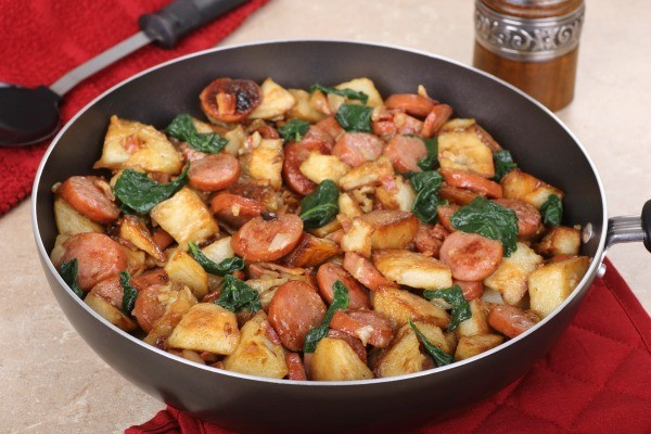 Skillet containing fried sausage and potatoes with onions and greens