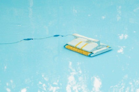 Close up of an automated swimming pool vacuum on the pool floor