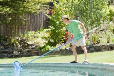 A man cleaning his backyard pool.