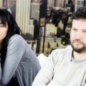 Man and woman sitting near each other with unhappy expressions