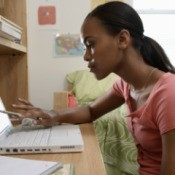 Young woman at a dorm room desk using a laptop