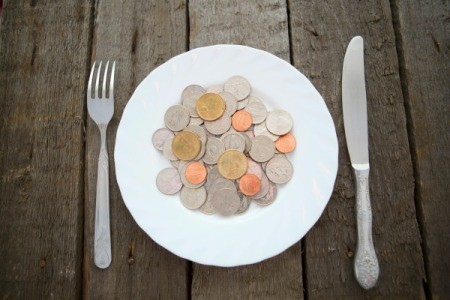 Pile of coins on a white plate with a knife and fork on a wooden table