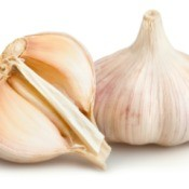 One full and one half bulb of garlic against a white background