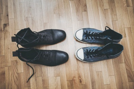 Pair of black boots and tennis shoes on a vinyl floor